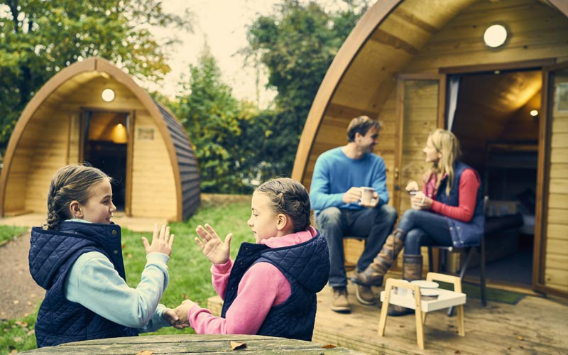 Family sitting outside a glamping Pod at Whitemead Forest Park