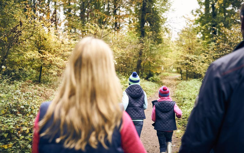 Family walking in Whitemead Forest Park in Autumn