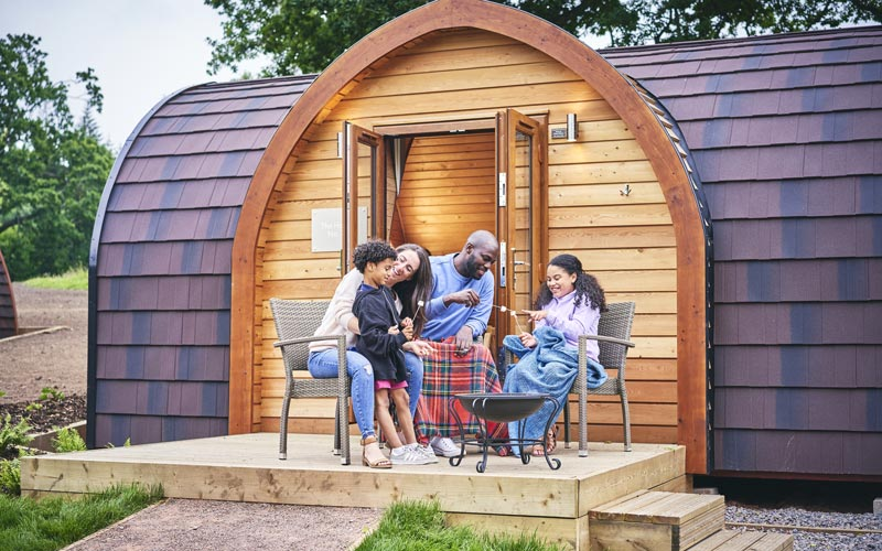 Family toasting marshmallows outside a glamping pod at Whitemead Forest Park